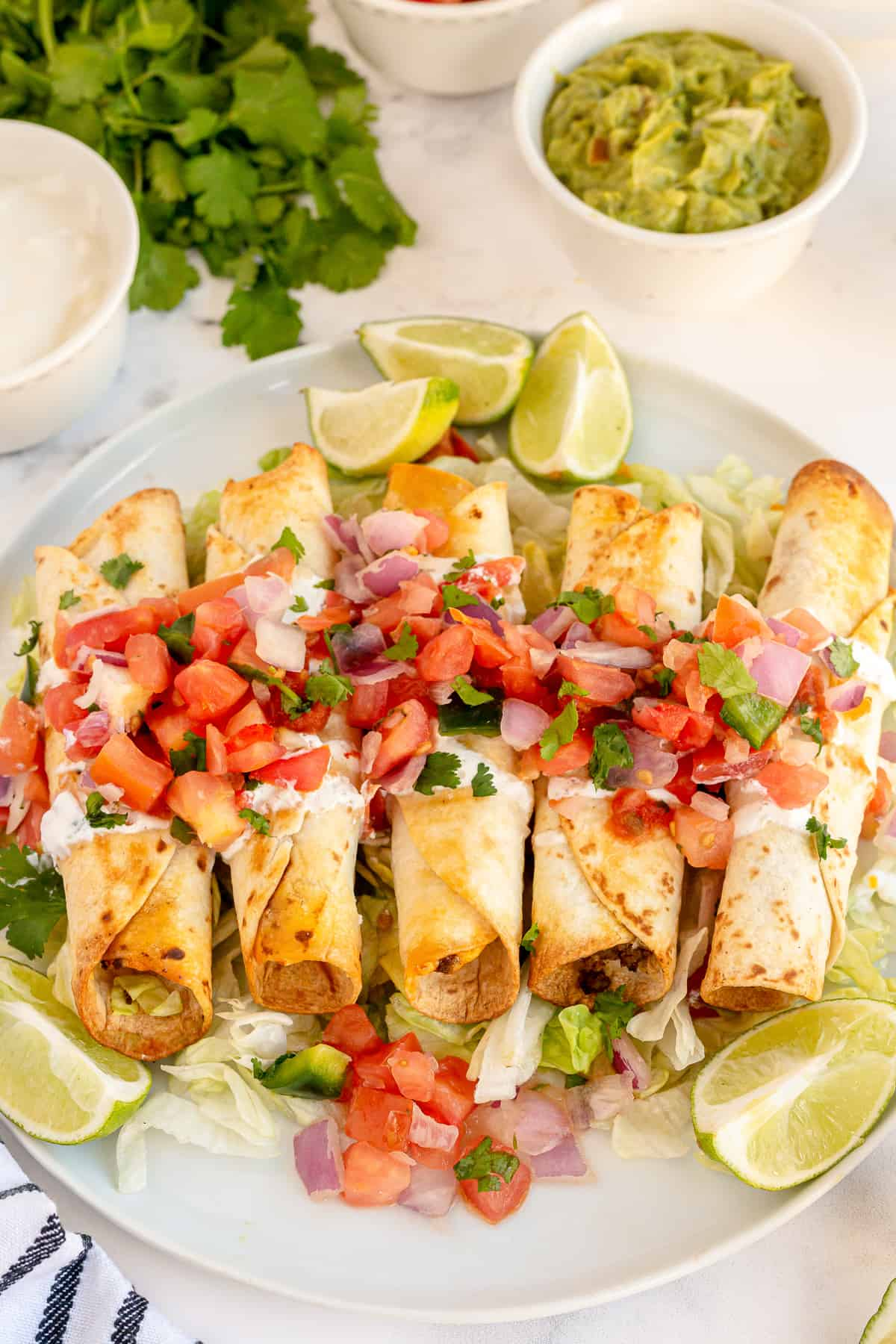 A platter of taquitos with toppings.