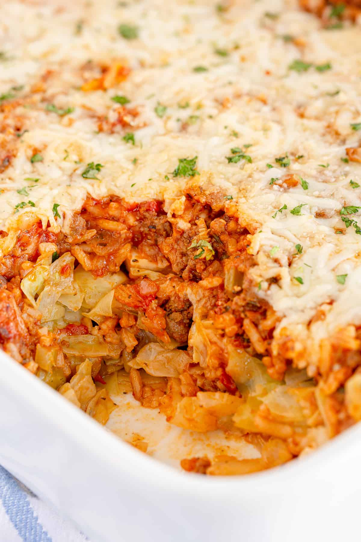 A casserole dish filled with Cabbage Roll Casserole with a scoop missing.