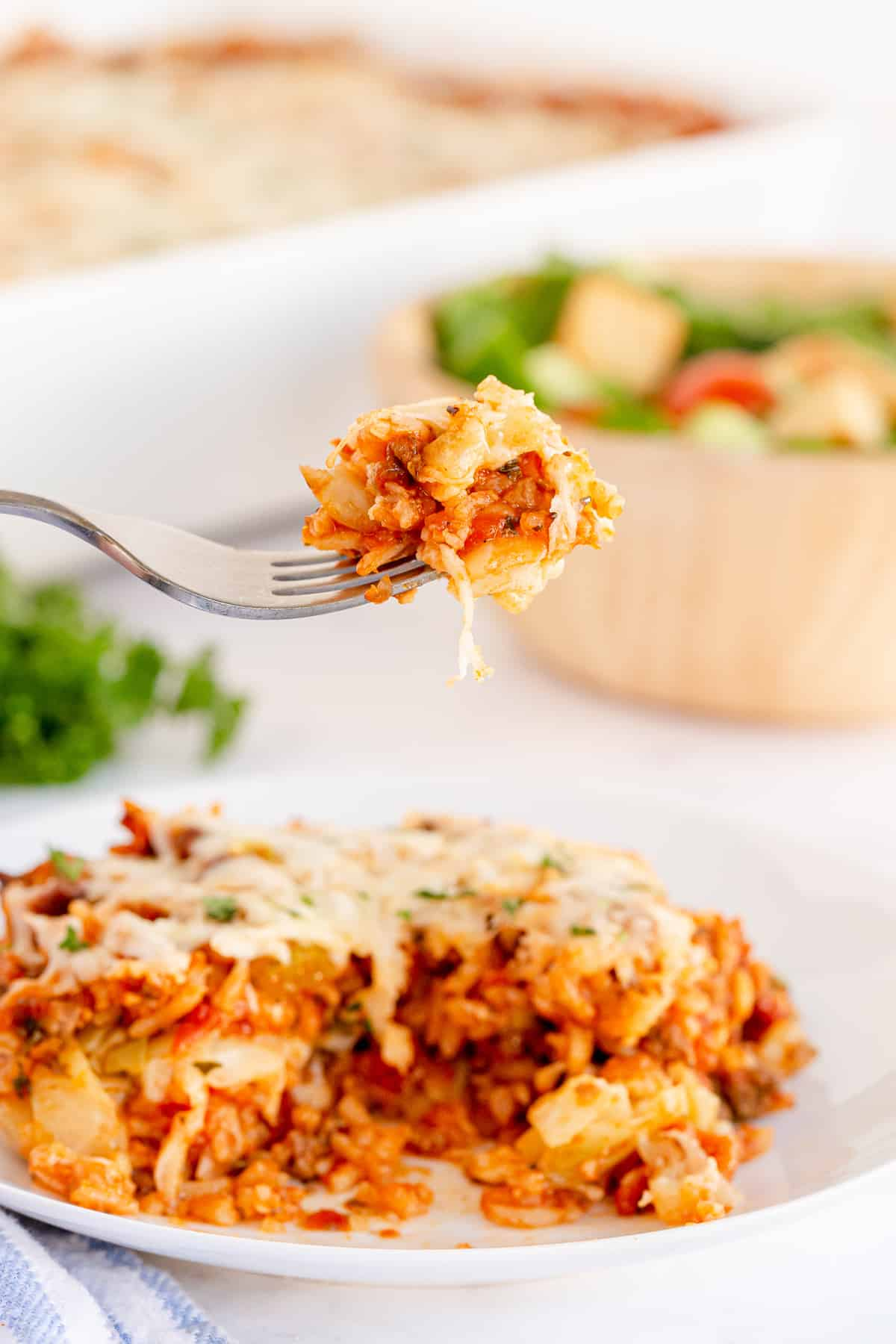 A fork lifts a bite of cabbage roll casserole from a white plate.