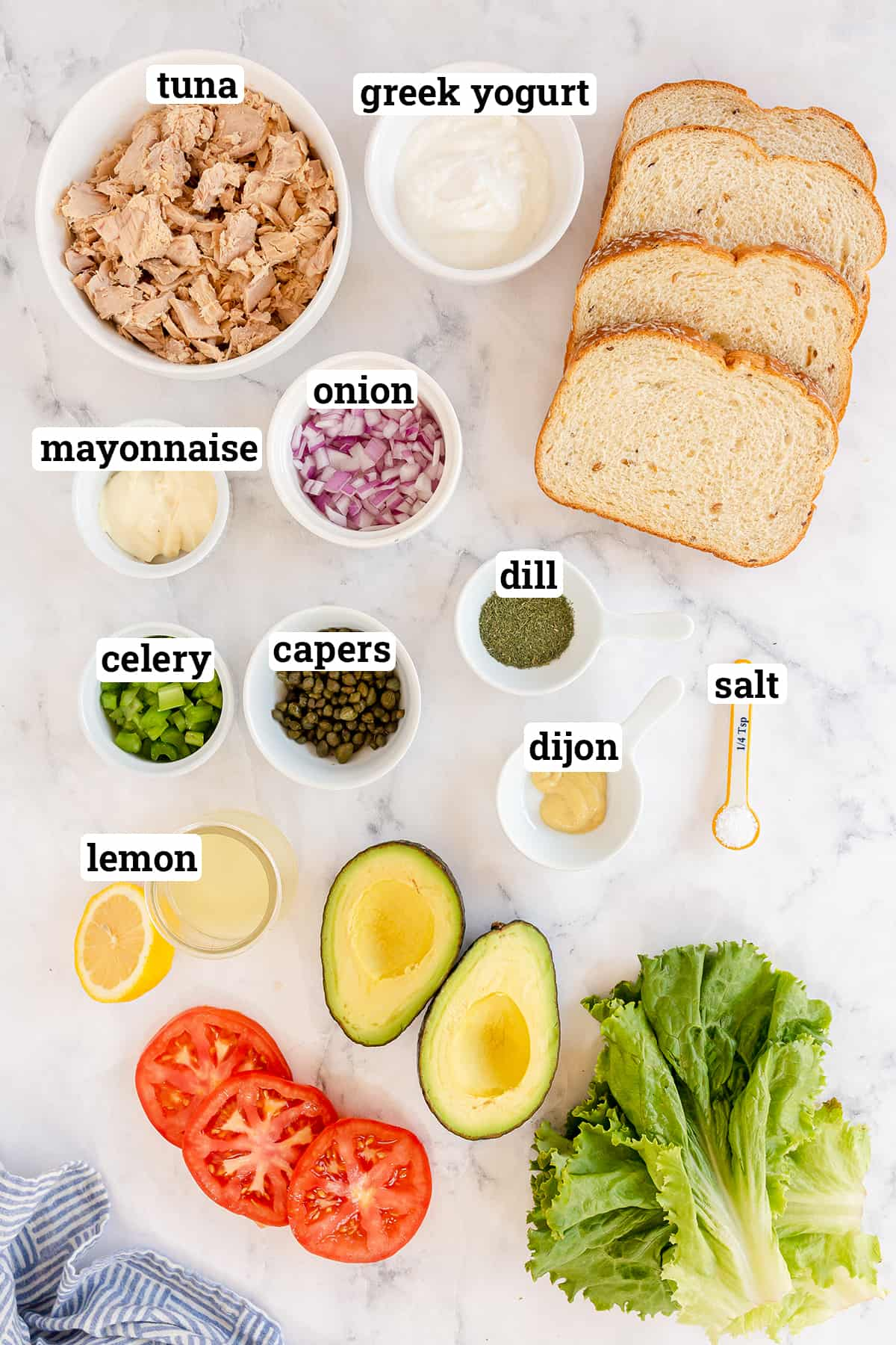 The ingredients to make tuna salad with capers and dill with overlay text.