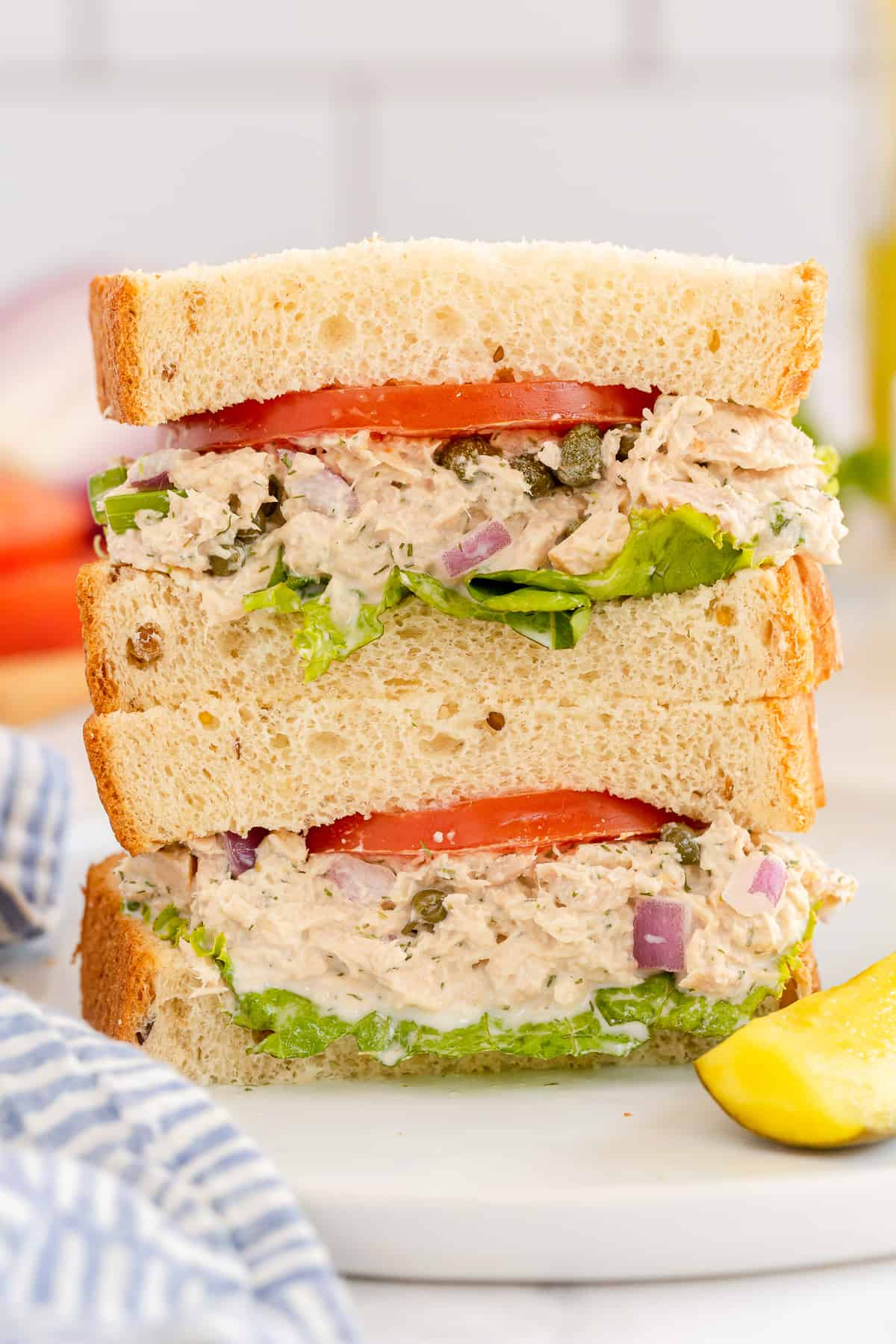 A tuna sandwich with tomatoes and lettuce cut in half and stacked on a plate.