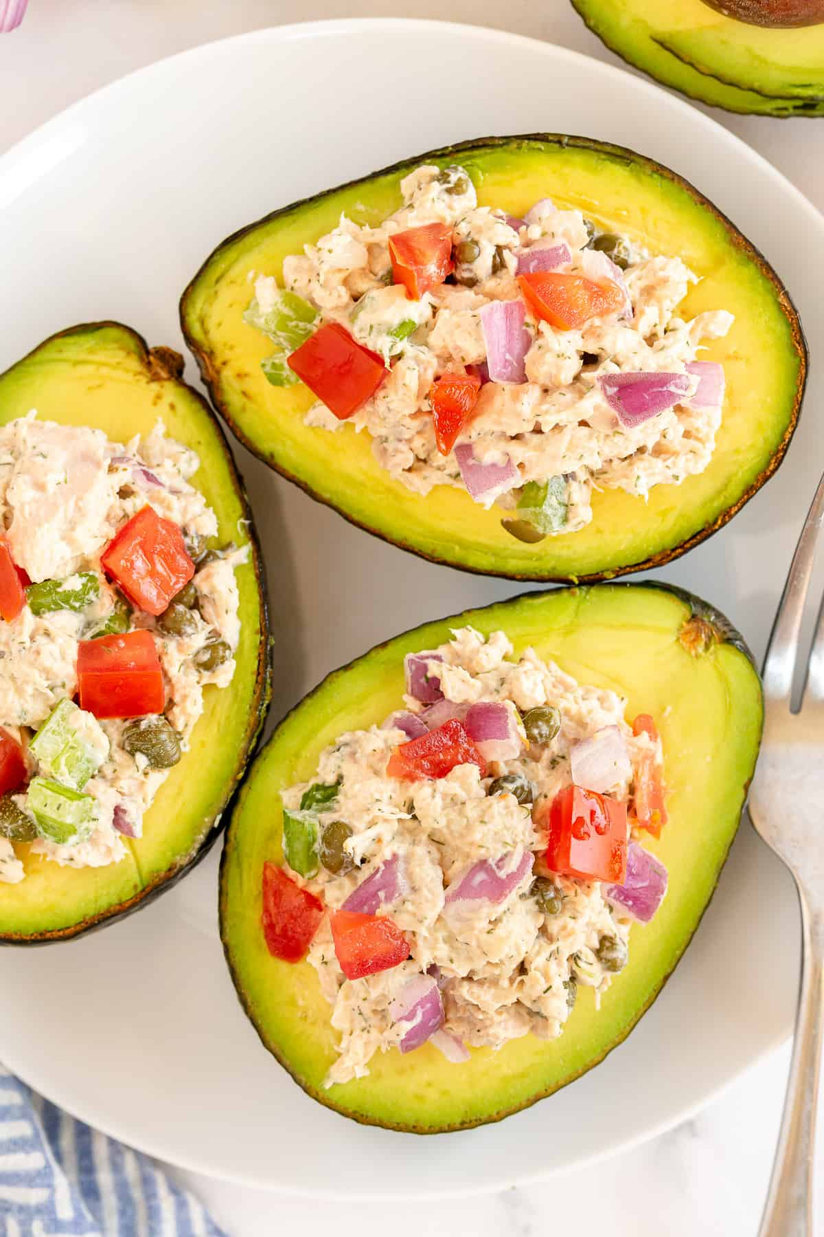 Three avocado halves stuffed with tuna salad.