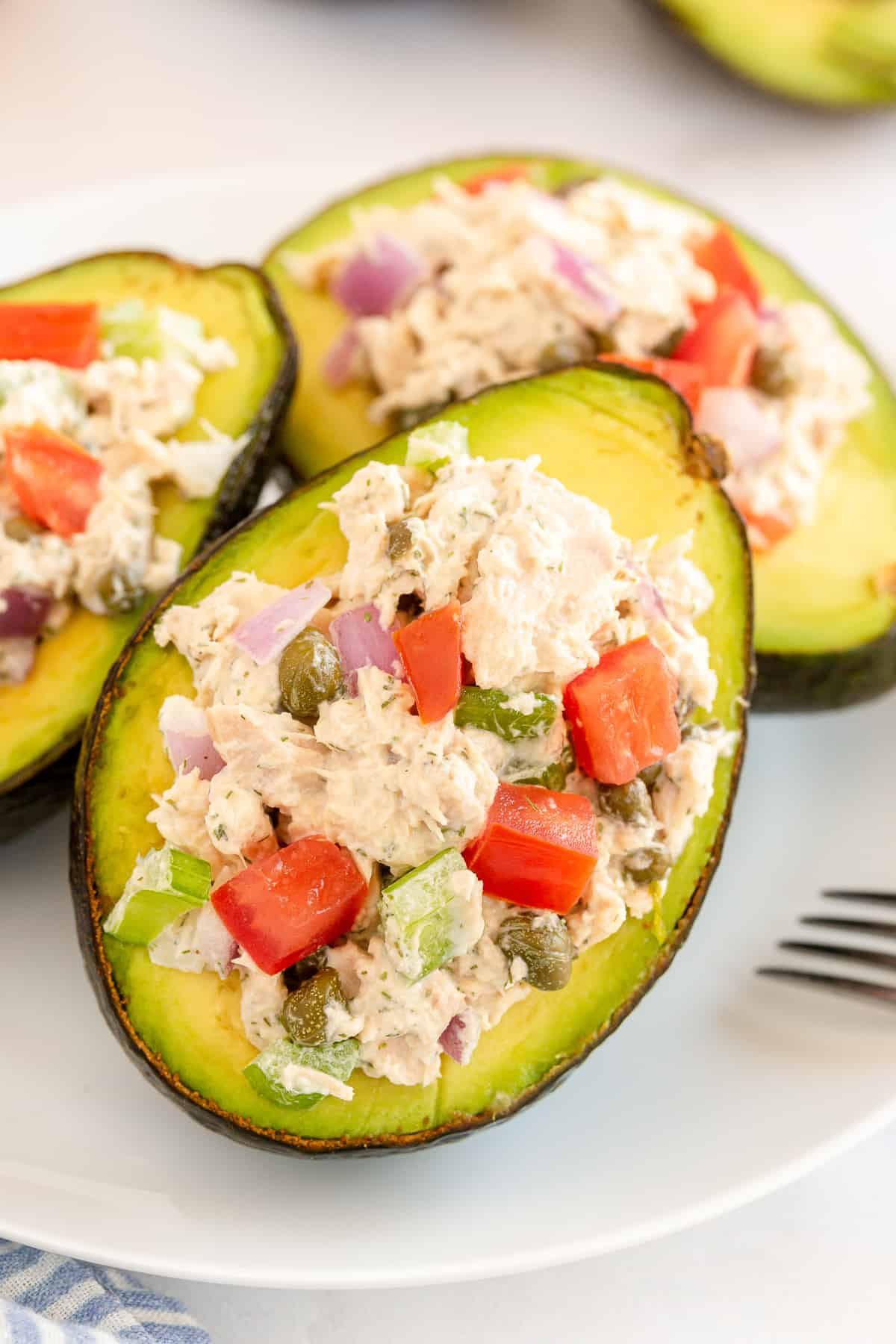 A half of an avocado stuffed with tuna resting on two others.