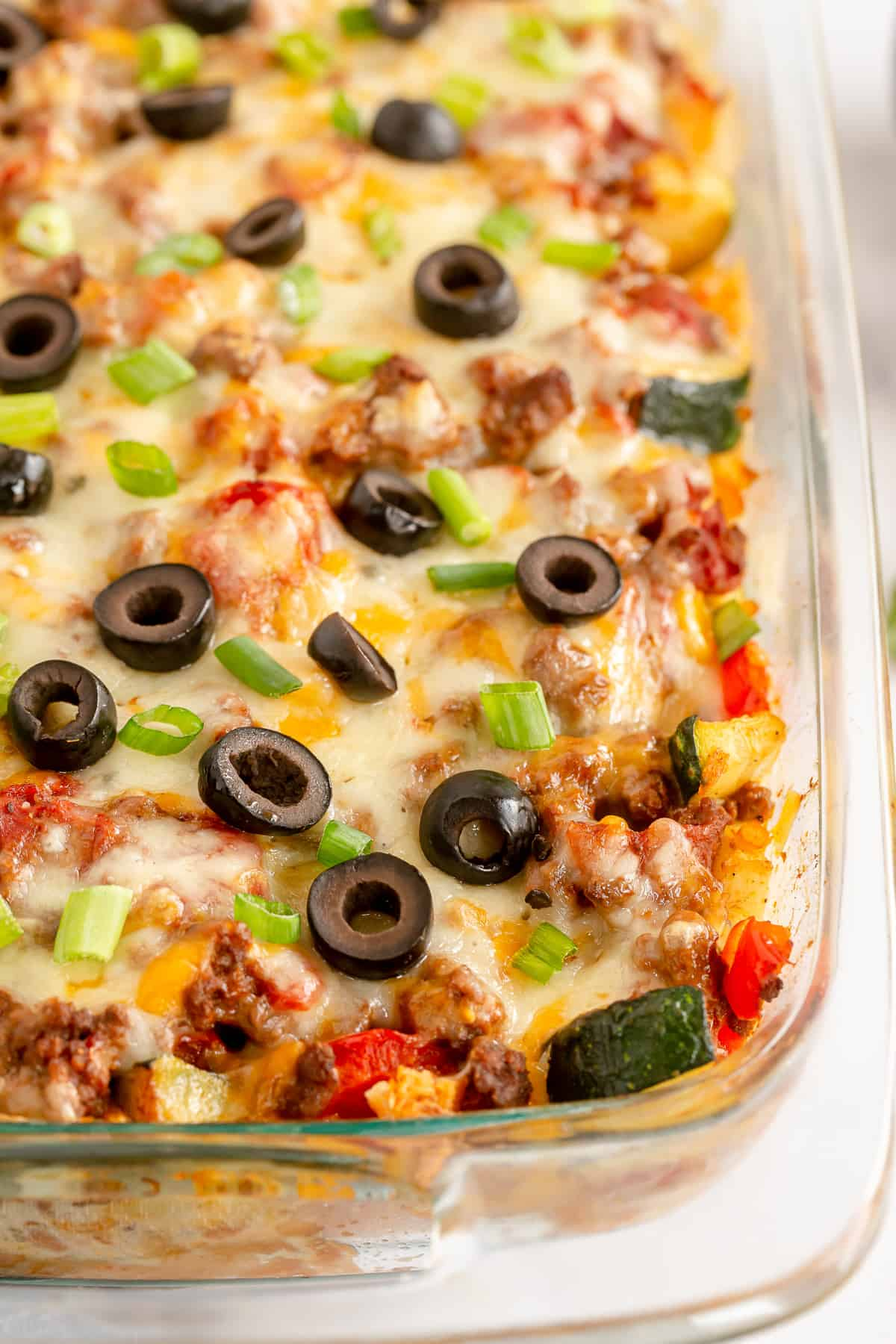 A closeup of the top of a Taco Bake casserole topped with olives.