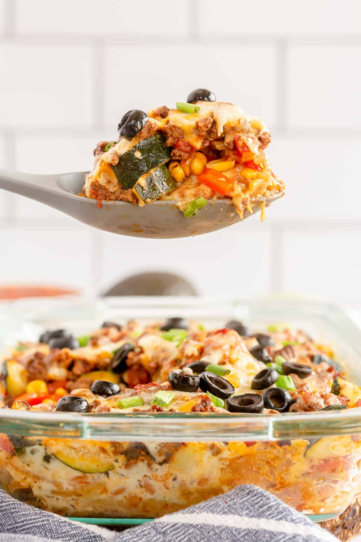 A spoon with a scoop of ground beef and vegetables hovers over a casserole dish.