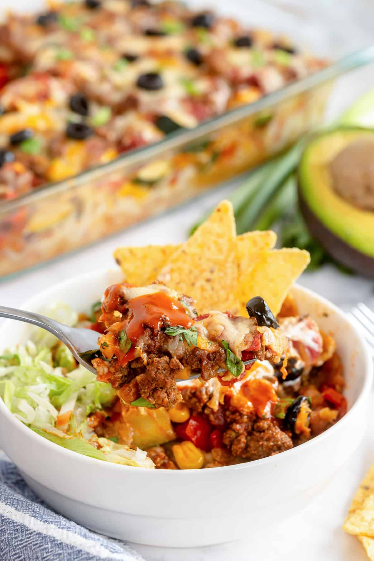 A fork digs into a serving of Beef and Vegetable Taco Bake.