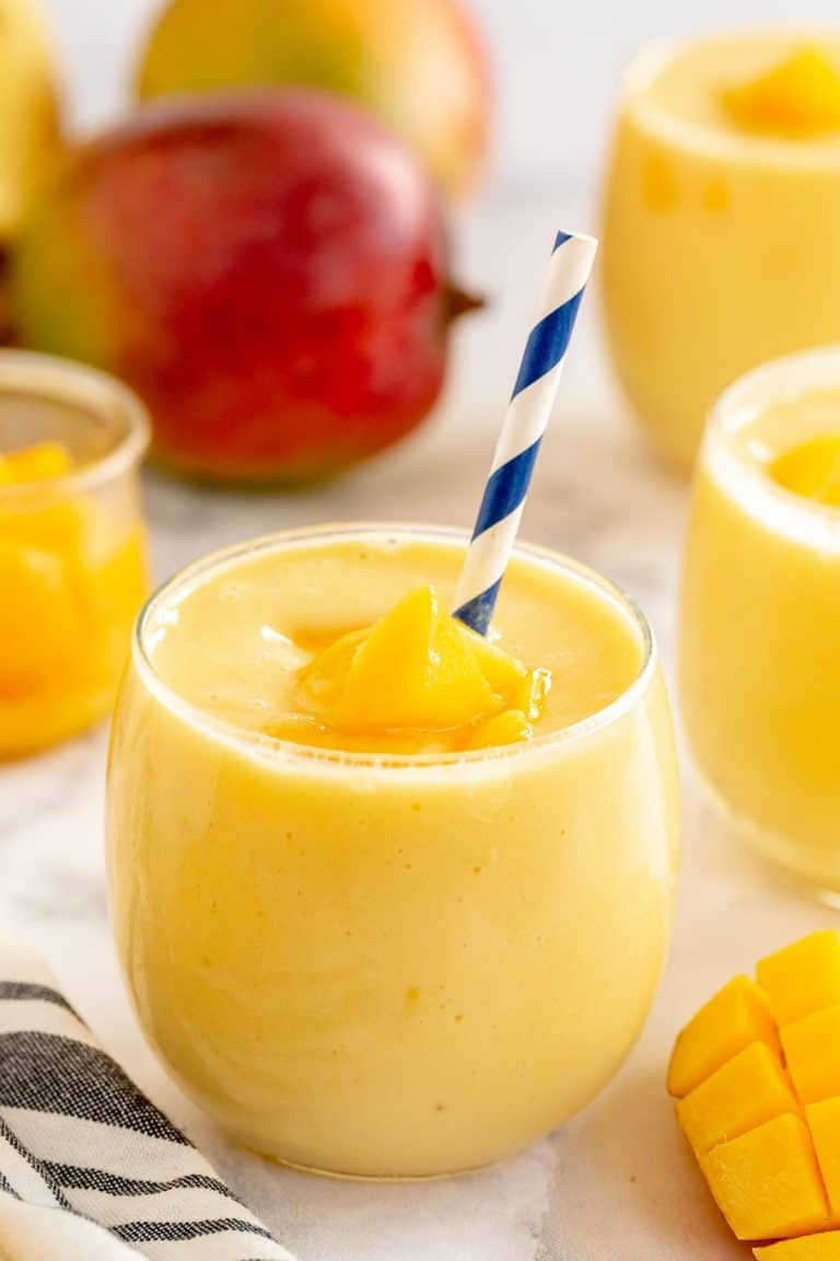 A mango smoothie in a small glass with a blue and white straw.