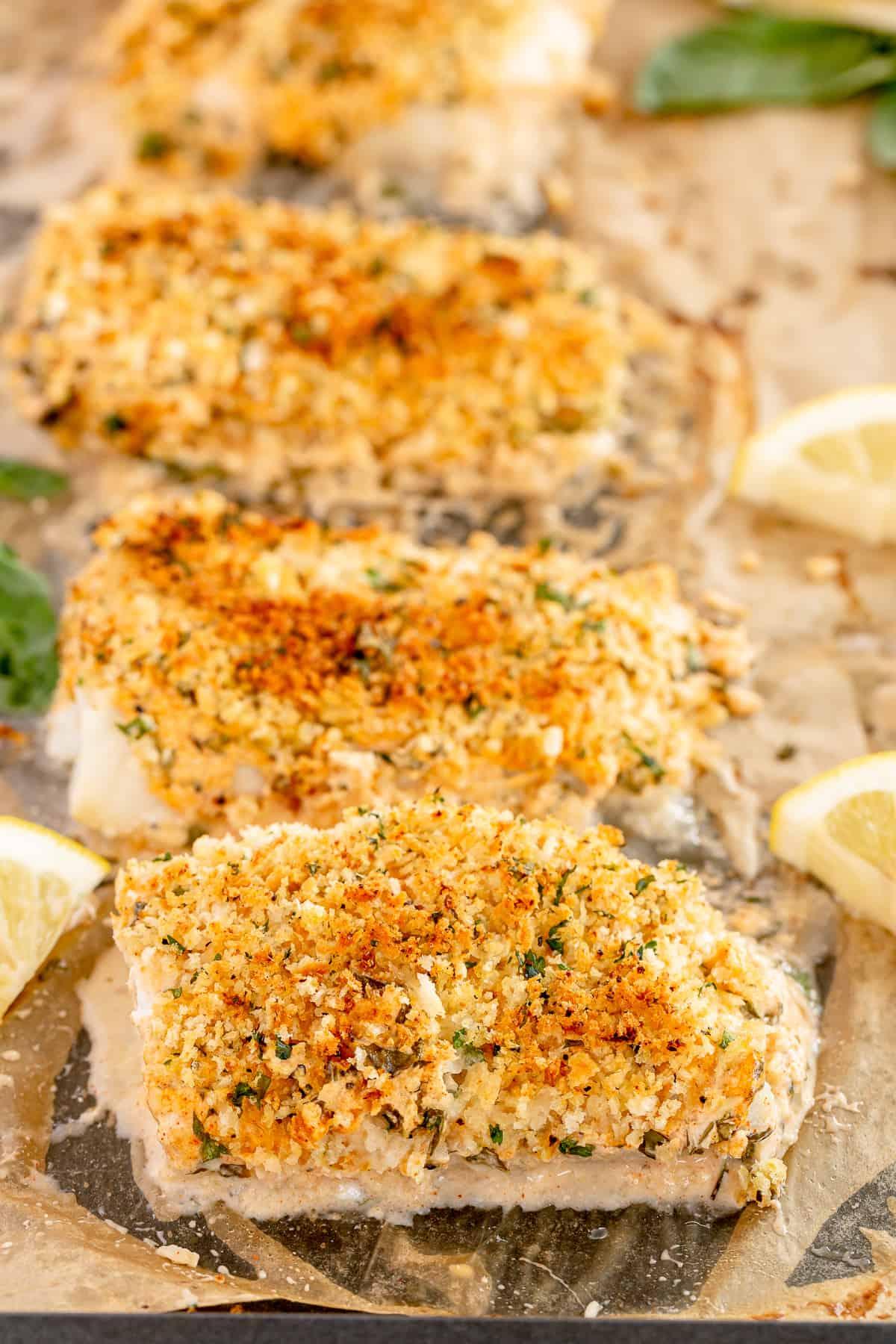 Four Lemon Basil Cod Fillets lined up on a baking sheet.