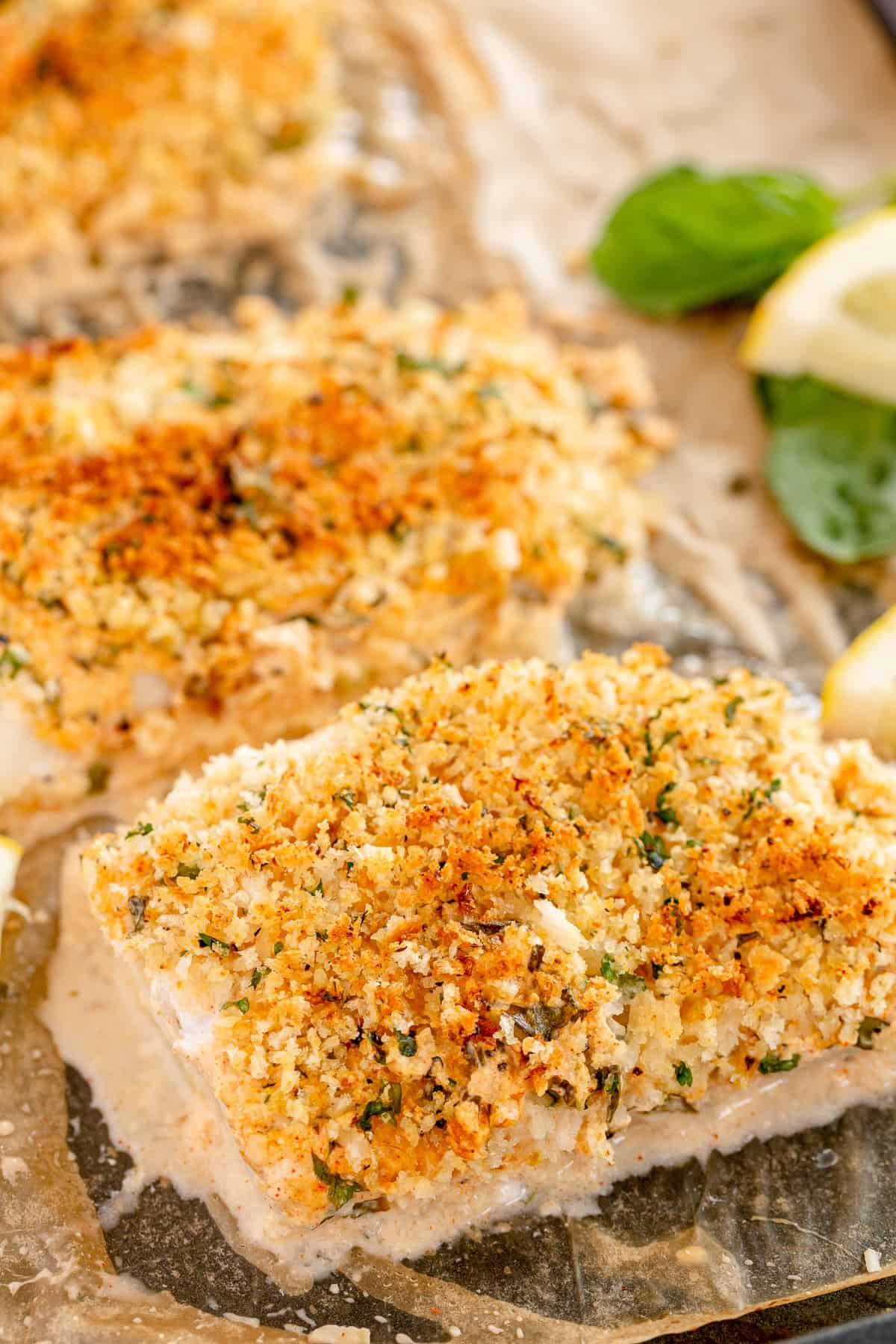 Breaded cod fillets on a parchment paper lined baking sheet.