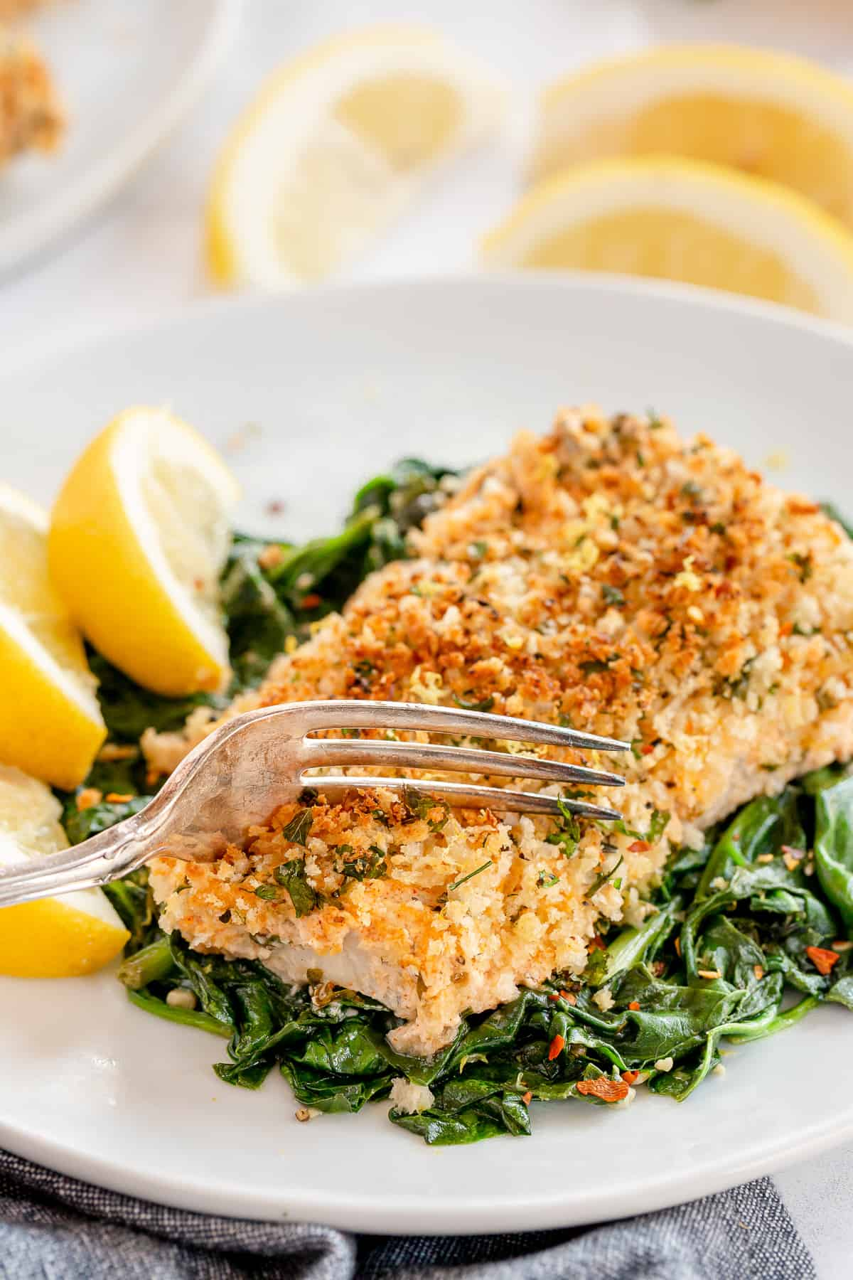 A fork presses down into Lemon Basil Cod on a bed of spinach.