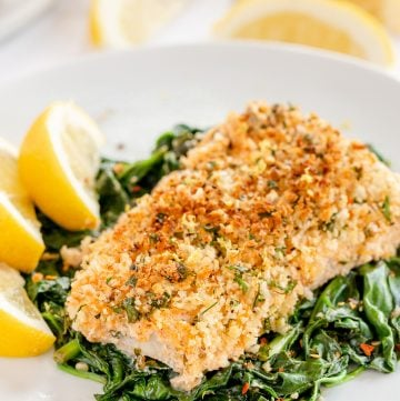 A Lemon Basil Cod Filet on a bed of spinach on a white plate.