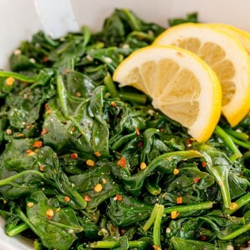 Sauteed spinach with crushed red pepper in a white bowl with lemon wedges.