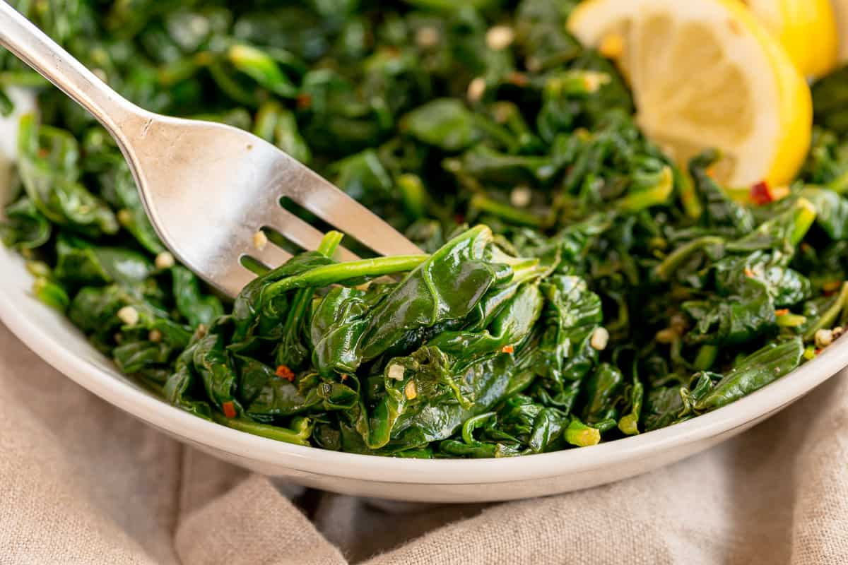 A fork digs into a bowl of Sautéed Spinach with Garlic and Lemon