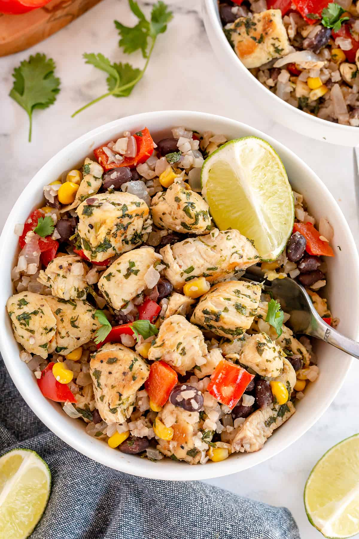 An over the top shot of chunks of cilantro lime chicken in a bowl with cauliflower rice, beans, and peppers.