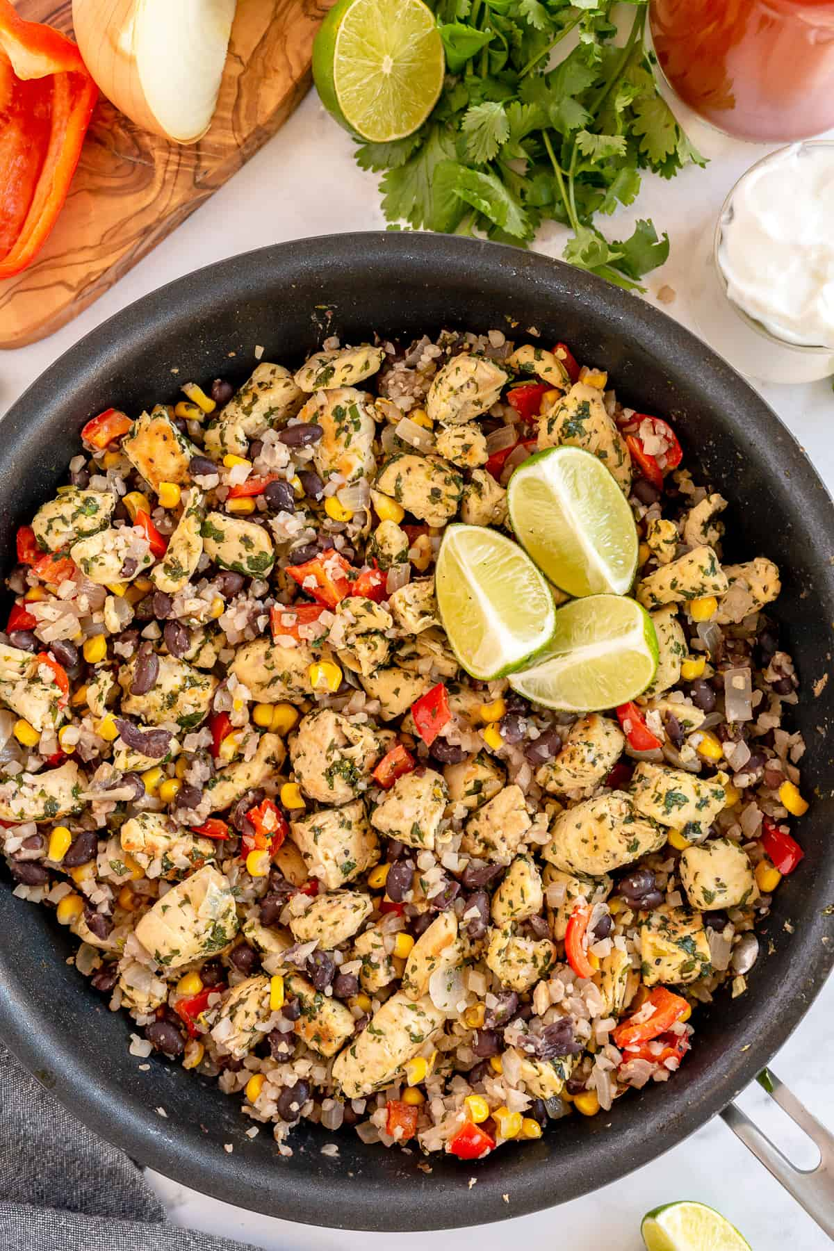 A skillet of Cilantro Lime Chicken with Tex-Mex Cauliflower Rice