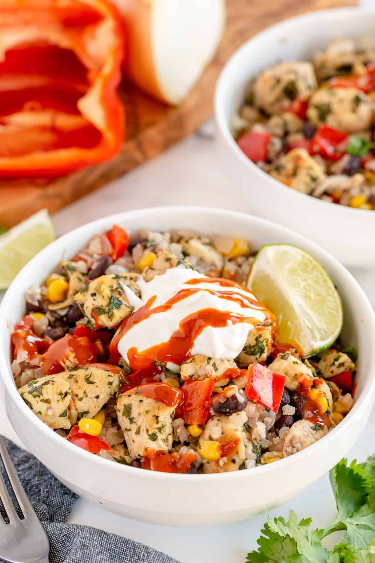 A Cilantro Lime Chicken Bowl topped with sour cream and hot sauce.