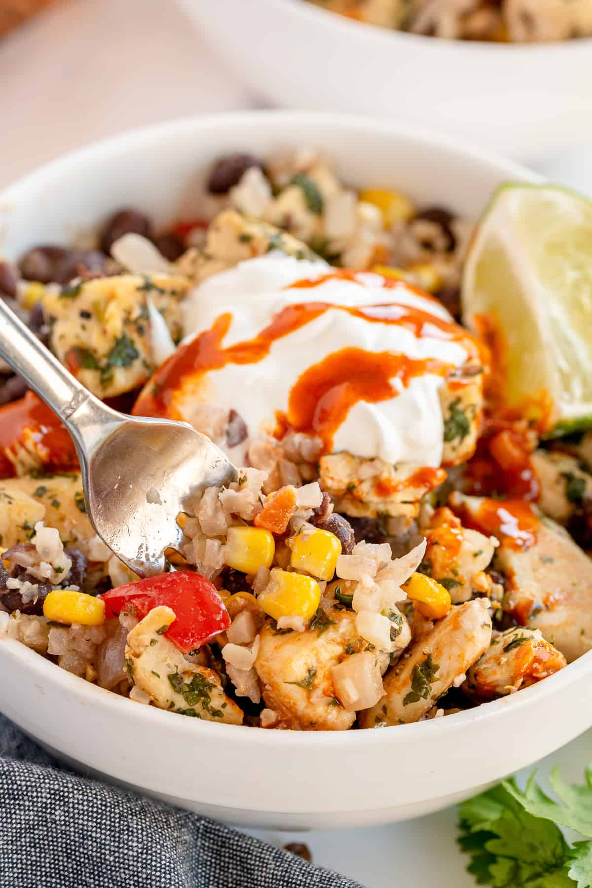 A fork digs into a Cilantro Lime Chicken Bowl topped with sour cream.