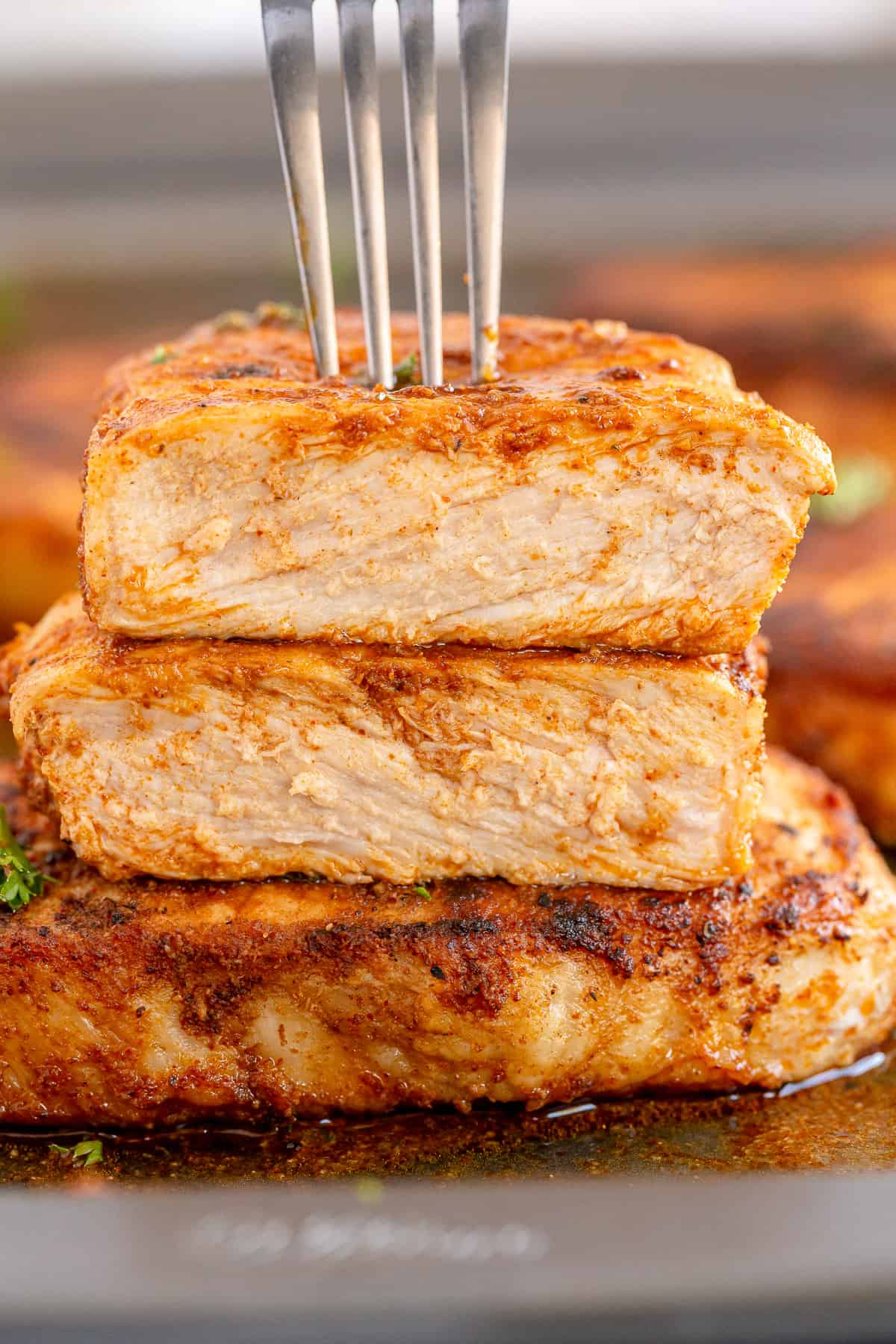 A fork pressing down on to a stack of pork chops.